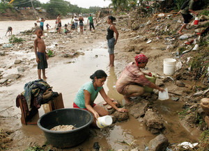 People wash their belongings in a river after flashfloods and mudslides hit outside of San Cristobal