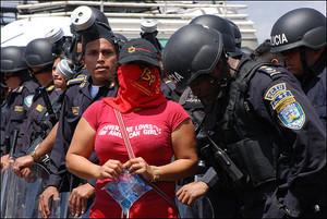 Militante del Bloque Popular tra agenti antisommossa (Foto Mirian Huezo)