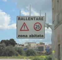 """Cartello stradale """"Rallentare zona abitata"""" e San Ferdinando di Puglia."""