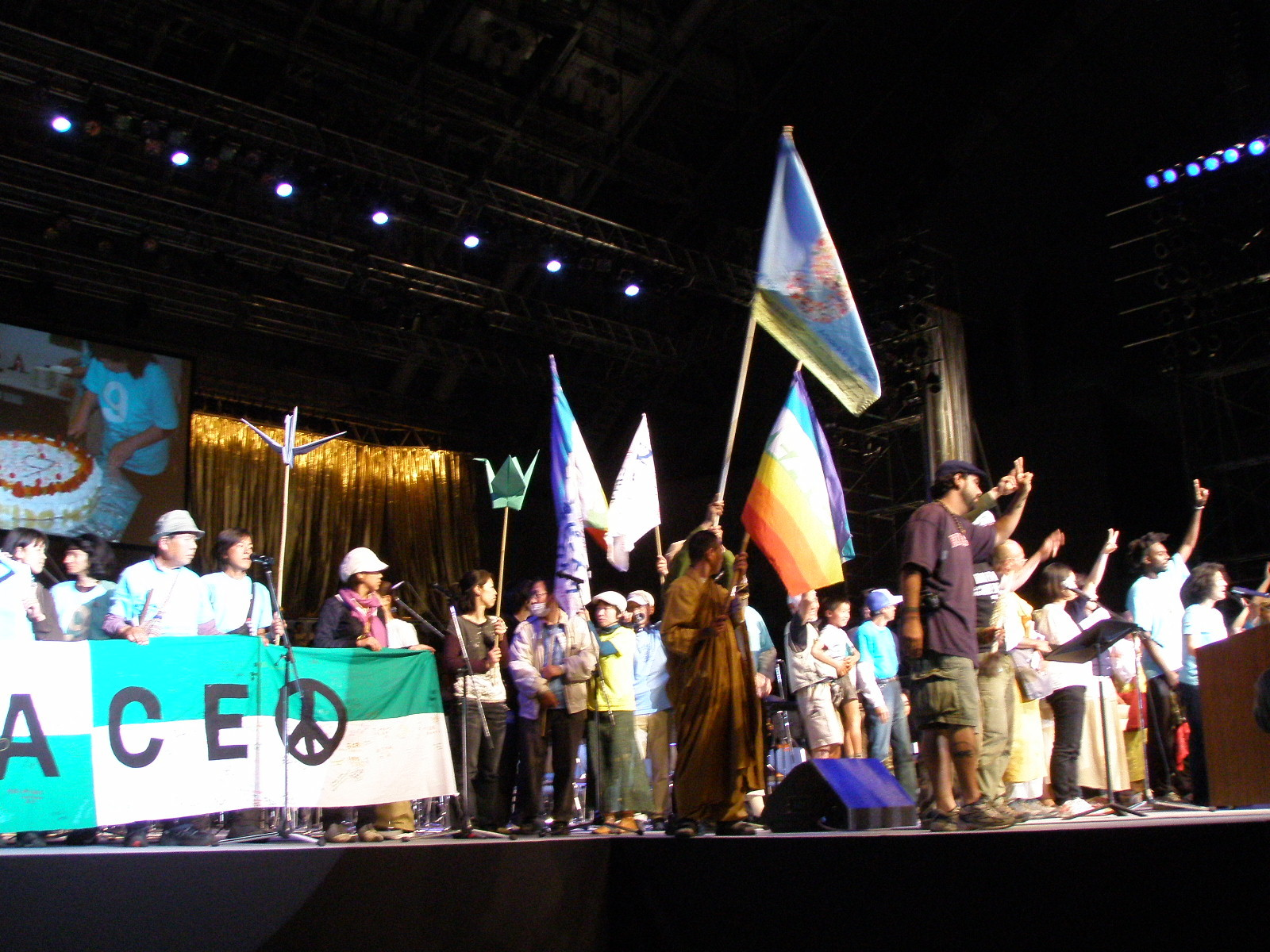"""Un gruppo nucleo di """"Peace Walk"""", arrivato da Hiroshima dopo più di 2 mesi di marcia per la pace, saluta dal palco i partecipanti alla conferenza"""