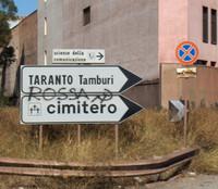 """L'indicazione del quartiere Tamburi, il quartiere a ridosso dell'area industriale di Taranto. Il color """"rosso ilva"""" dimostra il degrado ambientale. Le polveri di minerale che ILVA utilizza nel ciclo produttivo sono ormai ovunque."""