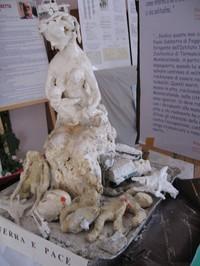 Statua realizzata da Paolo Sabbetta che rappresenta una donna che allatta il suo bambino, simbolo della vita, mentre la guerra ha lasciato distruzione, morte, ferite indelebili e vite segnate.