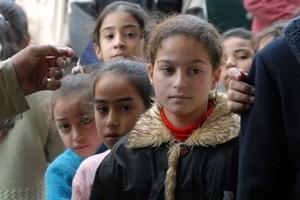 Alcune bambine e bambini in fila per un pezzo di pane. La guerra a Gaza è anche questo