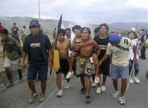 Un gruppo di indigeni trasporta un ferito, dopo gli scontri con la polizia.