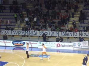 """Lo striscione con la scritta in inglese """"Ferma il disastro ambientale a Taranto ora"""""""