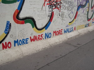 "A popular slogan graffitied on one of the sections of the East Side Gallery, reading: ""No more wars. No more walls. A united world."""
