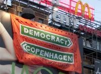 Have a watch of our banner action from the 17th December in Copenhagen's central square.  The police scrambled a helicopter and brought 20 police and 3 vans down to arrest our two climbers. They were released the following day.  The banner drop was covered as breaking news live on Danish DR channel who were in the square at the time.  The COP15 process is not democratic. Until we have negotiations that are, we will never reach just or sustainable agreements on climate change or any other g