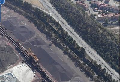 """Colline di minerali di ferro altri minerali e carbone a pochi metri dalle case del """"quartiere Tamburi"""" a Taranto"""