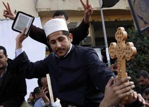 Un religioso musulmano tiene in mano il Corano e una croce Cristiana durante un momento della preghiera comune che si e' svolta al Cairo