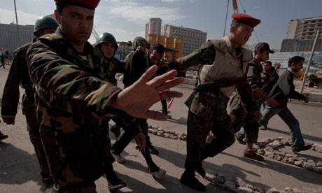 Gli ufficiali dell'esercito scortano un prigioniero lontano da Tahrir Square al Cairo, in Egitto. I militari - accusati di coinvolgimento in torture - hanno sempre sostenuto di essere una forza neutrale nel conflitto.