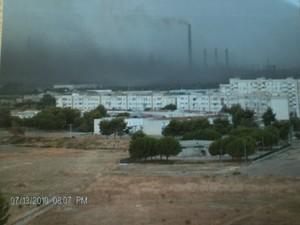 L'Ilva vista dal quartiere Paolo VI di Taranto in una giornata di vento. I parchi minerali della fabbrica sono scoperti e la polvere dei minerali sommerge sia i lavoratori sia i cittadini delle case del quartiere Tamburi