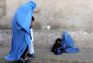 Una donna afgana con il suo bambino chiedono l'elemosina nella città di Herat. La situazione delle donne afgane è preoccupante.