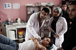 Il Dottor Housam Moustafa, un medico tirocinante, cura un ribelle siriano nella clinica di Reyhanli, in Turchia.