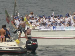 """L'arrivo dei nuotatori (di spalle). Sull'imbarcazione si legge la scritta """"BASTA ASPETTARE, VOGLIAMO CAMBIARE"""""""