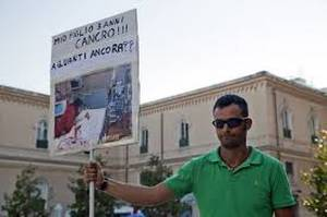 Mauro Zaratta sul palco nel 2012 a Taranto con il cartello