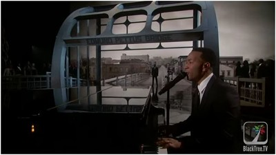 """Los Angeles, 22 febbraio 2015. Il musicista Common, sullo sfondo dell'Edmund Pennet Bridge, e John Legend al piano prima dell'attribuzione dell'Oscar per """"Glory"""""""