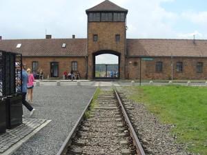 Ingresso del campo di sterminio di Birkenau, con immagine in primo piano delle rotaie che conducono al suo interno.