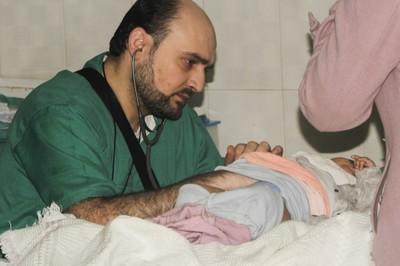 Il dottor Maaz visita una piccola paziente presso l'ospedale pediatrico di Aleppo