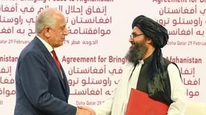 Il negoziatore Usa, Zalmay Khalilzad (a sinistra), firma l'accordo con il rappresentante dei telebani, Abdul Ghani Baradar (a destra nella foto)