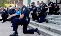 Poliziotti americani in ginocchio davanti ai manifestanti