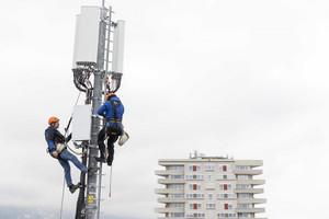 Operai al lavoro mentre installano antenne per comunicazioni mobili 5G