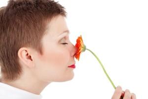 Donna che odora un fiore