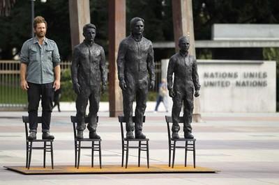 """CELEBRI WHISTLEBLOWERS: Scultore Davide Dormino in piede sulla sua scultura-installazione """"Anything to Say?"""", che raffigura (da destra) Chelsea Manning, Julian Assange, Edward Snowden."""