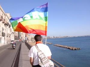 La bandiera della pace alla testa della Carovana della Pace; lungo la ringhiera dell'affaccio a mare di Taranto Vecchia camminano in fila indiana circa settanta pacifisti e di missionari. Sullo sfondo