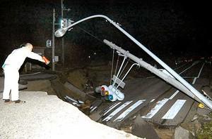 Un giapponese guarda sconcertato i danni causati dal terremoto alla strada a Tochio, nord-ovest del Giappone (Ap)