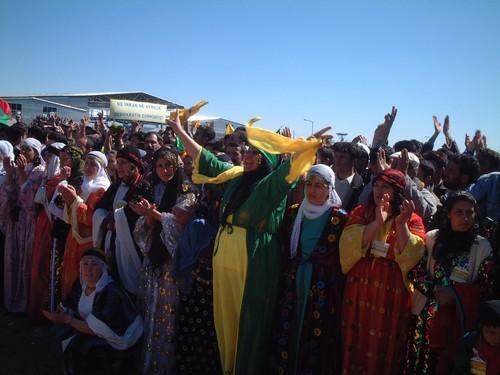 Nello spiazzo antistante il palco, una folta schiera di donne e ragazza vestite con abiti tradizionali curdi