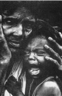 Mamma povera con in braccio un bambino che piange.
