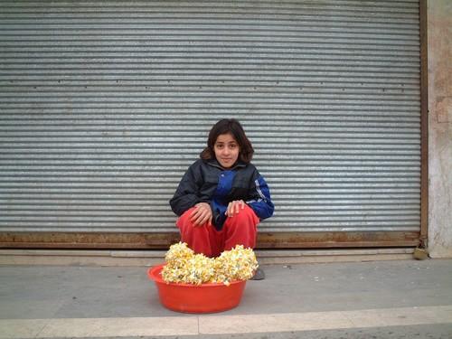 Bambina curda vende fiori all'angolo della strada