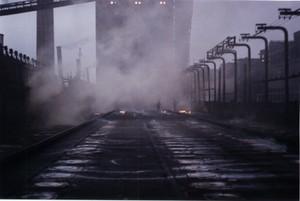 Foto 9 - Cokeria: piano coperchi. Si vedono sullo sfondo alcuni operai sommersi dal fumo e circondati da lingue di fuoco. Può sembrare una scena dell'inferno dantesco.