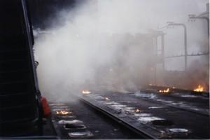 Foto 7 - Cokeria. E' il reparto più inquinante del centro siderurgico. Questo è il piano coperchi. Dai forni fuoriescono fumi parzialmente incendiati. I fumi non dovrebbero fuoriuscire in quanto cance