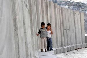 Due bambini palestinesi giocano vicino al muro costruito per separare Israele dalla Palestina.