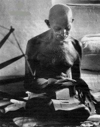 Foto di Gandhi che legge seduto sul pavimento.