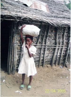 Una bambina di Kenge che porta sulla testa un sacco con i tuberi di manioca.