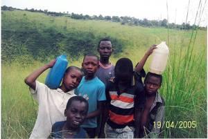 Bambini che tornano che tornano da una delle poche sorgenti nelle vicinanze di Kenge
