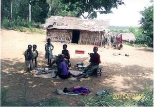"""Scena di convivialità. La mamma sta preparando il pranzo (""""luku"""" a base di manioca) che consumeranno seduti sulla stuoia."""