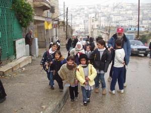 Membri dell'Ass. Christian Peacemaker Teams accompagnano alcuni bambini palestinesi a scuola attraversando con loro i territori israeliani.