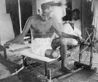 Foto che ritrae Gandhi intento a filare