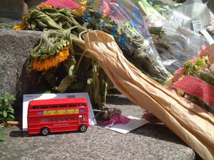 Un modellino di autobus insieme a dei fiori lasciati vicino Tavistock Square