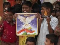 i ragazzi si sono messi in posa esibendo il loro desiderio di pace: la colomba abbraccia il mondo con le ali e la bandiera indiana sembra abbracciarlo.