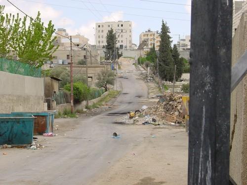 Betlemme: campo profughi di Aida. E' ben visibile la postazione israeliana (dopo il muro in fondo alla strada) con la torretta mimetizzata da un telo. I palazzi da cui sparano i cecchini sono quelli d