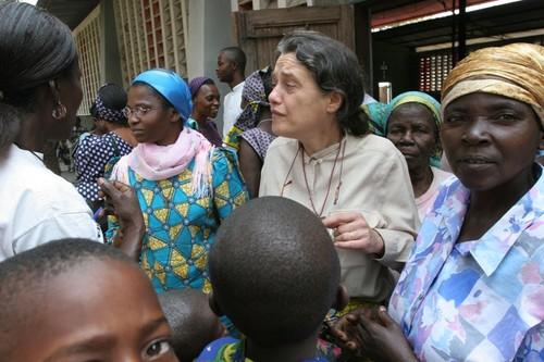 Chiara attorniata dalle gente all'uscita dalla messa domenicale a Kenge. Molti e continui sono i problemi posti e le richieste di aiuto.