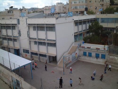 Bethlehem: campo profughi di Aida. La scuola delle Nazioni Unite, crivellata dei colpi degli israeliani. Piu' sotto, i bambini giocano.