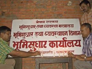 Pittori che cancellano i cartelli che indicano 'governo di sua maestà' e scrivono 'governo del Nepal'.