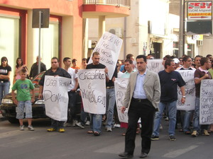 Un'immagine della manifestazione. I cartelli [fogli scritti a mano] chiedono un maggior impegno alla città verso le persone che - anche se extracomunitarie - sostengono la sua economia.
