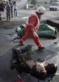 Un membro della Croce Rossa Libanese cammina vicino ad un corpo brutalmente bruciato dopo la distruzione del porto di Beirut, bersaglio dell'aviazione Israeliana, 17 luglio