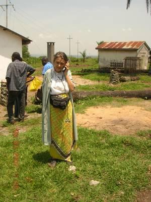 Chiara Castellani, con il telefono satellitare, avvisa gli amici che la prima lampadina è stata accesa a Kimbau